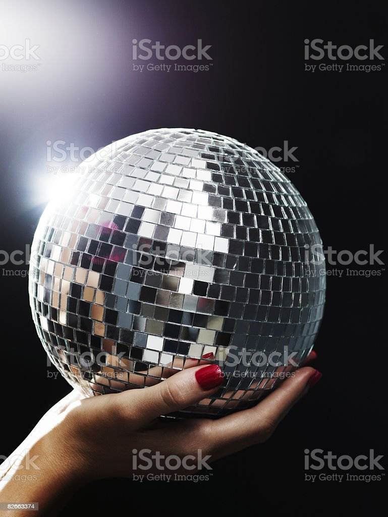 Hands holding small mirror ball up towards light stock photo