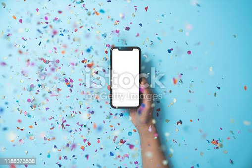Hands holding smart phone on blue background