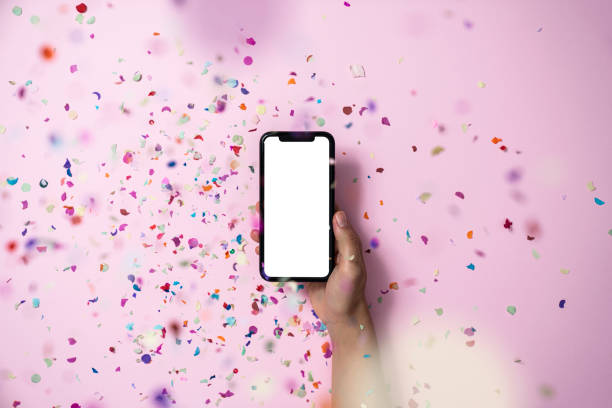 Hands holding smart phone on pink background stock photo