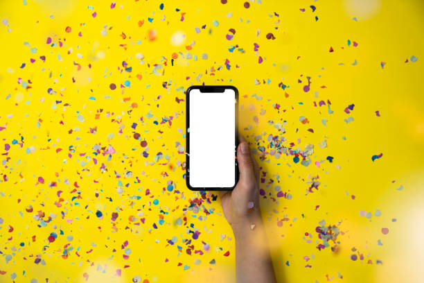 Hands holding smart phone on yellow background stock photo