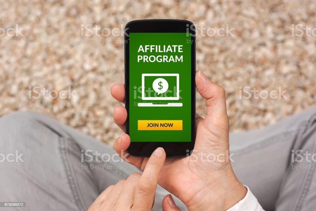 Mains tenant un téléphone intelligent avec affiliation concept de programme sur écran photo libre de droits