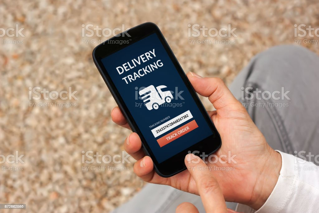 Hands holding smart phone with delivery tracking concept on screen stock photo