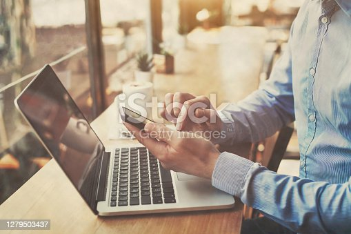 istock hands holding smartphone in cafe, banking online, freelancer 1279503437