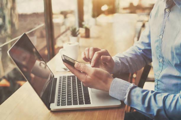 hands holding smartphone in cafe, banking online, freelancer stock photo