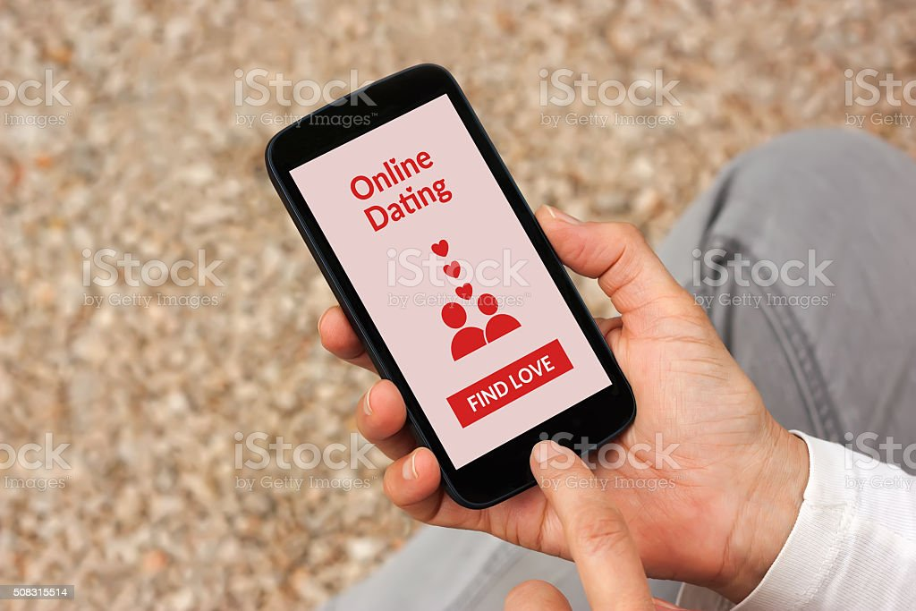 Hands holding smartphone with online dating application mock-up on screen stock photo