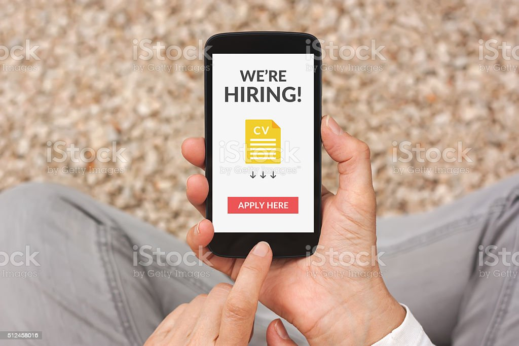 Hands holding smartphone with we are hiring concept on screen stock photo