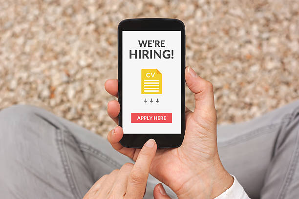 hands holding smartphone with we are hiring concept on screen - apply online stock photos and pictures