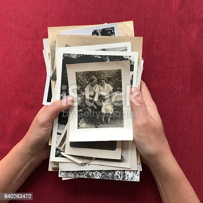 Hands holding stack of old photographs.   iPhone