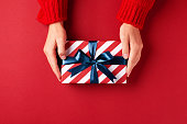 istock Hands holding striped gift box. 1048398122