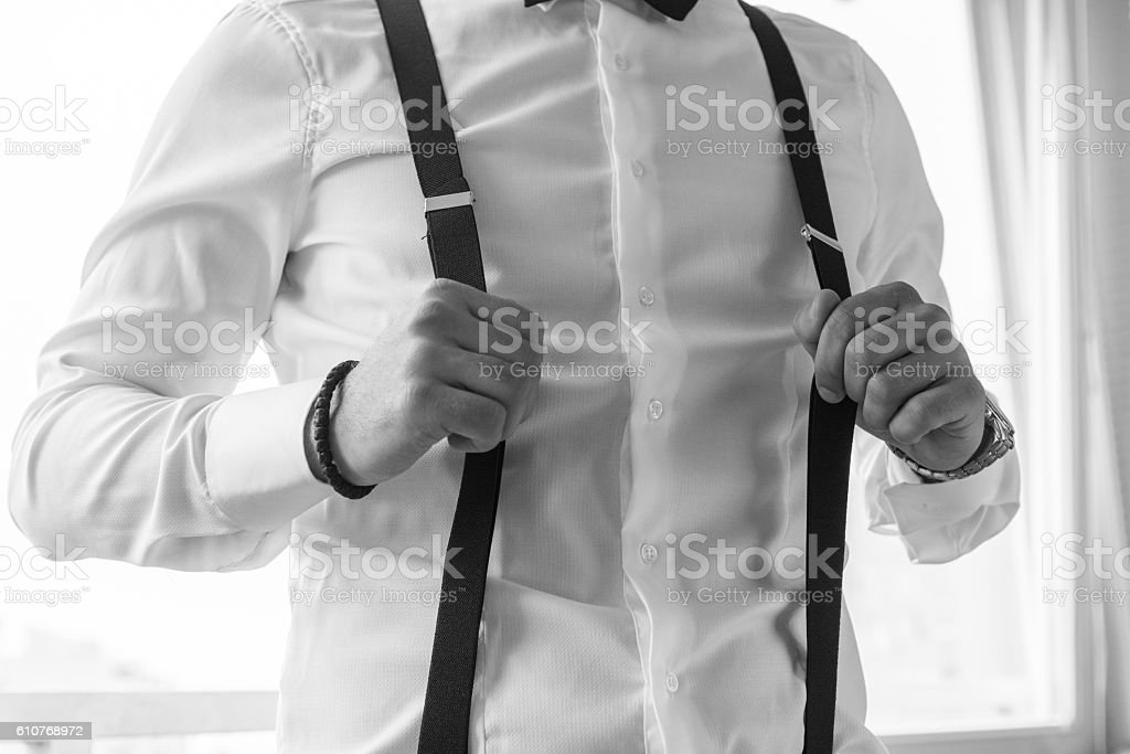Hands holding suspenders. - Photo