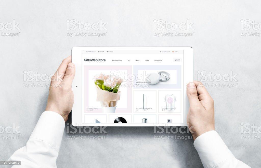 Hände halten Tablet mit Geschenken Webstore mock-up auf dem Bildschirm – Foto