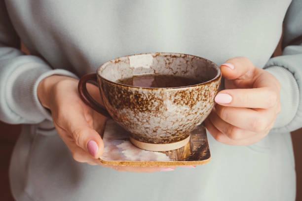 hands holding tea mug stock photo