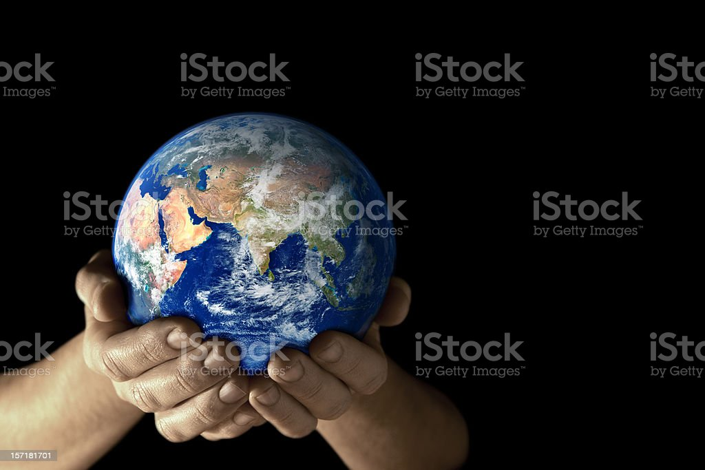 Hands holding the earth facing East on black background royalty-free stock photo