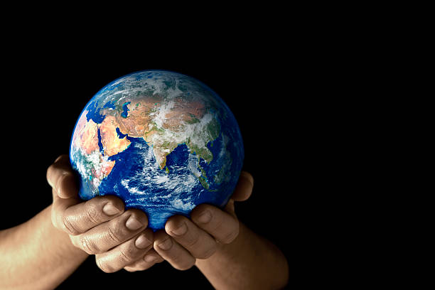 Hands holding the earth facing East on black background stock photo