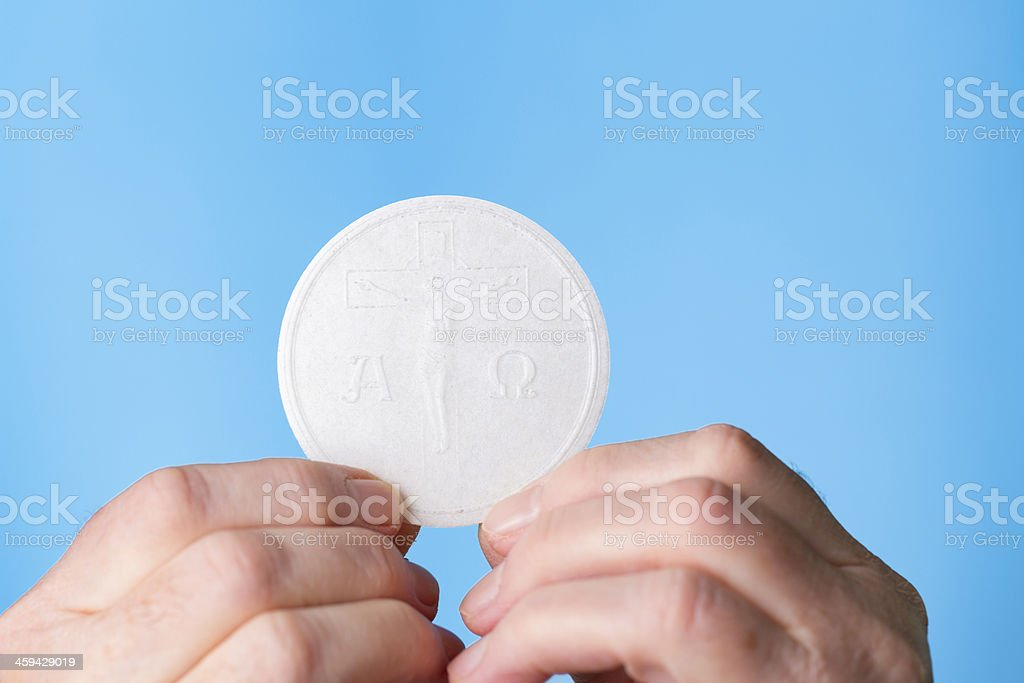Hands holding the holy Eucharist on a blue background stock photo