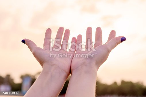 974882202istockphoto hands holding the sun at dawn 540981392