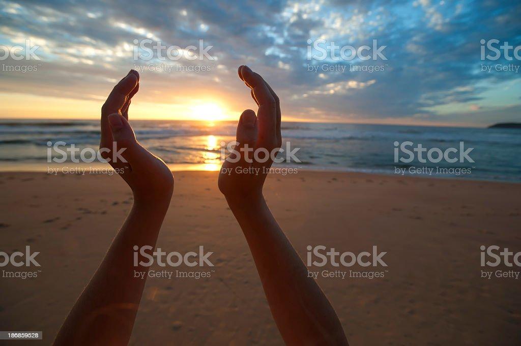 Hands holding the sunrise stock photo