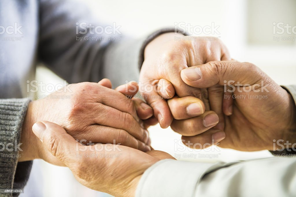 hands holding together stock photo