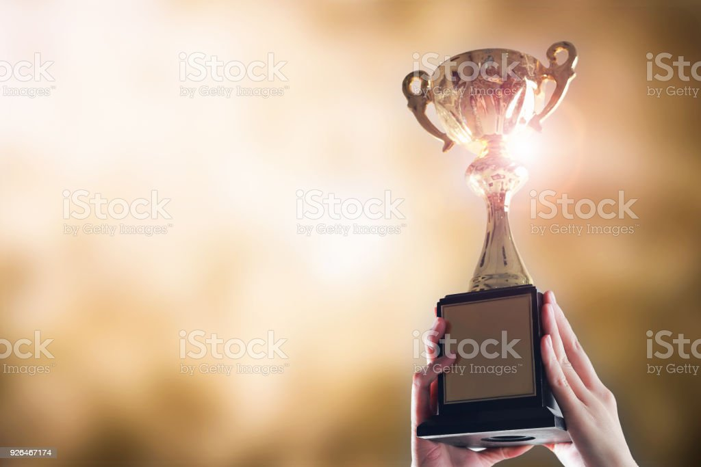 Hands holding trophy cup on gold blurry bokeh background. stock photo