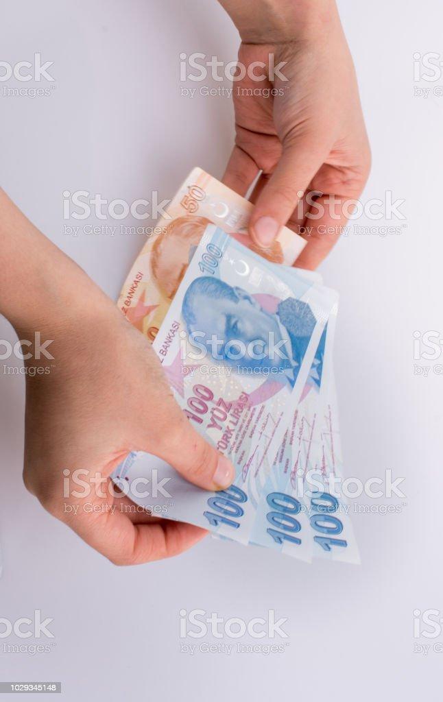 Mãos segurando as notas de Lira ilhas ao lado das notas de dólar americano - foto de acervo