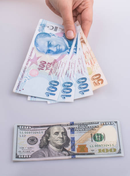 Hands holding Turksh Lira banknotes by the side of American dollar banknotes stock photo