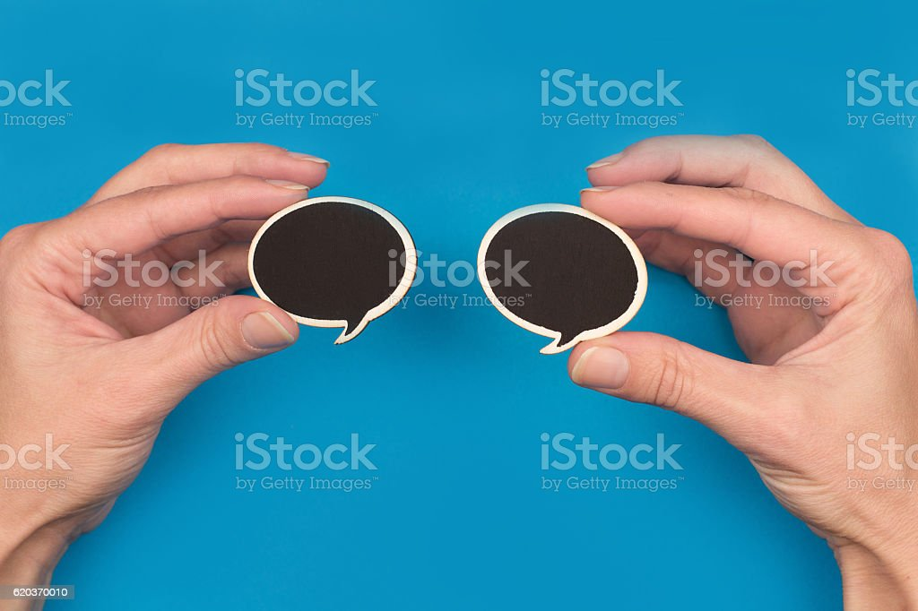 hands holding two black speech bubbles on blue background zbiór zdjęć royalty-free