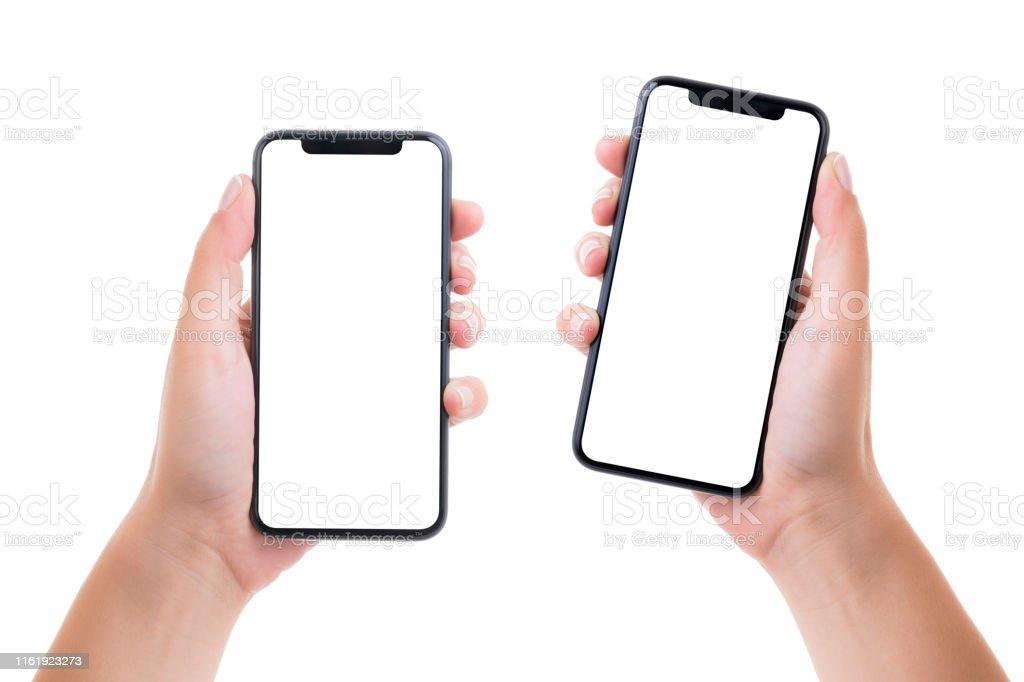 Mãos que prendem dois telefones espertos da tela branca em branco - Foto de stock de Adulto royalty-free