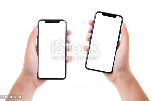 Woman hands holding two blank white screen smart phones on white background. Isolated on white.