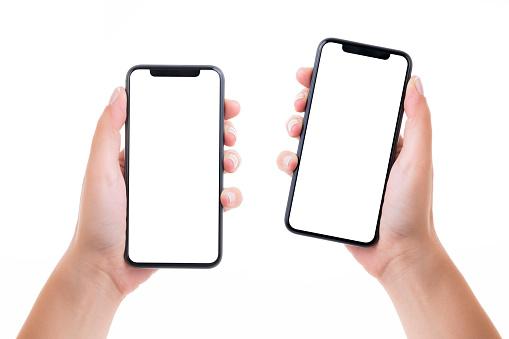Foto de Mãos Que Prendem Dois Telefones Espertos Da Tela Branca Em Branco e mais fotos de stock de Adulto