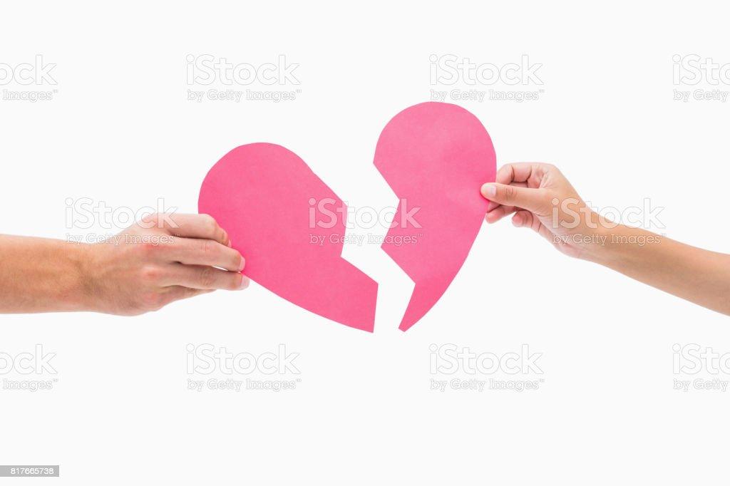 Hands holding two halves of broken heart stock photo
