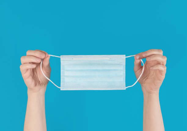 handen die een blauw gezichtsmasker omhoog houden, dat tegen een heldere blauwe achtergrond wordt geïsoleerd - verduisterd gezicht stockfoto's en -beelden