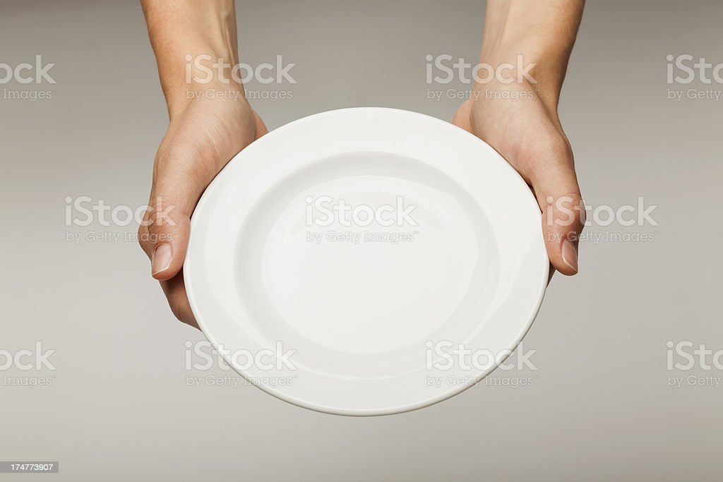 Hands holding up an empty white plate stock photo