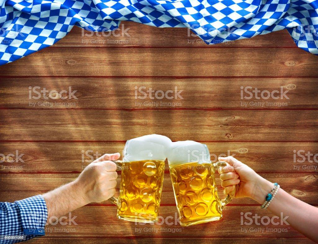 Manos sosteniendo jarras de cerveza debajo de la bandera bávara - foto de stock