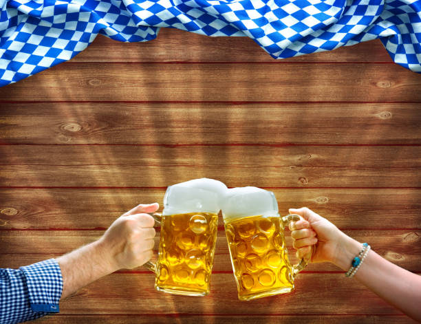 manos sosteniendo jarras de cerveza debajo de la bandera bávara - oktoberfest fotografías e imágenes de stock