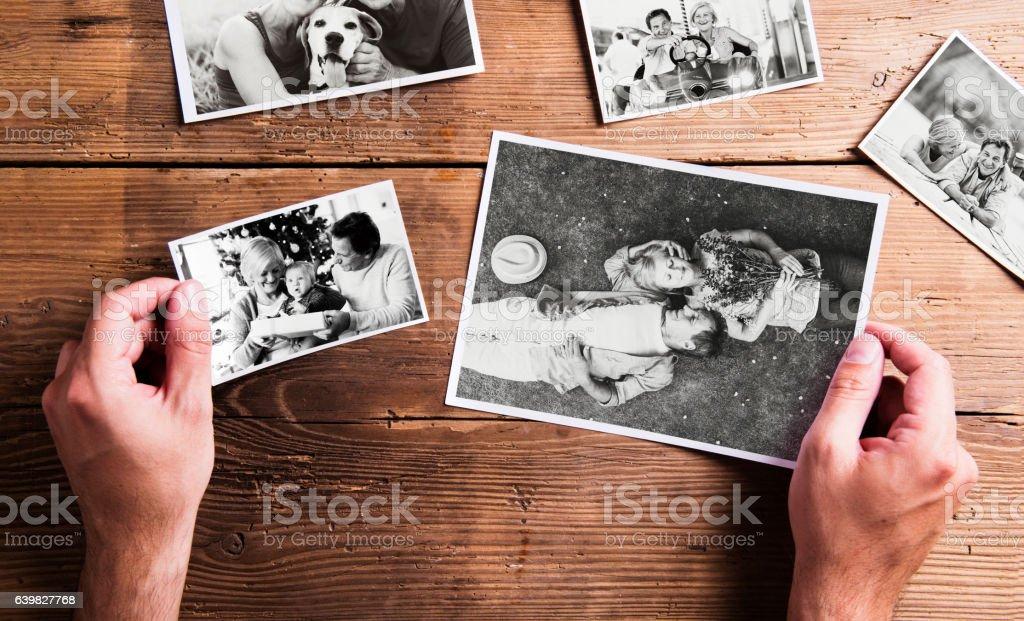 Hands holding various pictures of senior couple. Studio shot, wo stock photo