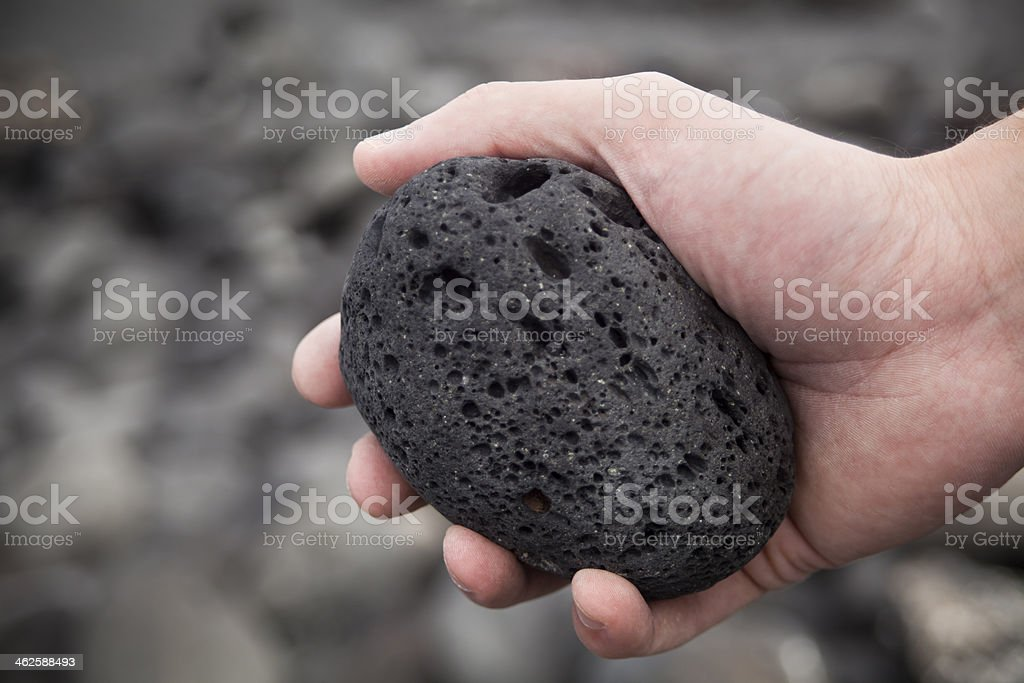 Hands holding volcanic stone stock photo