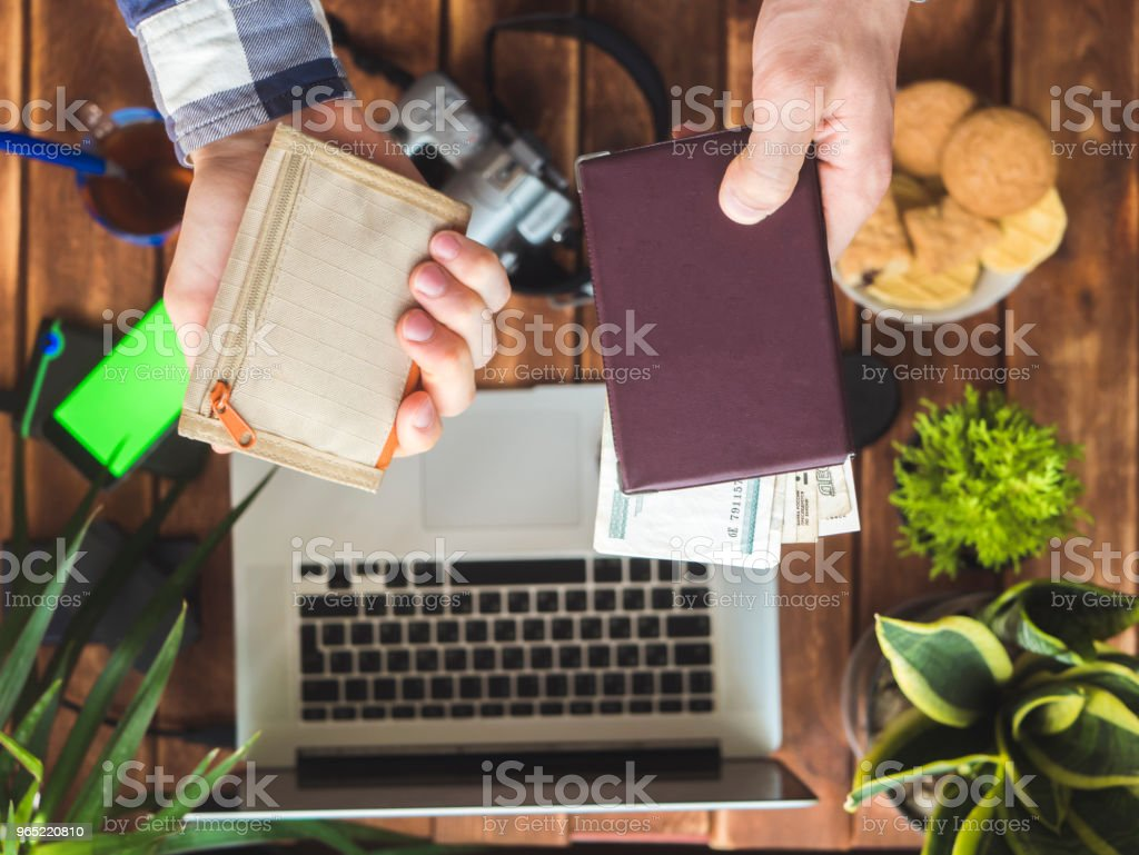 hands holding wallet and passport with cash money over table with photo devices royalty-free stock photo