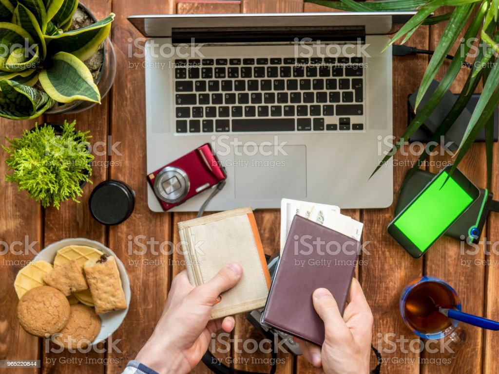 hands holding wallet passport and cash over wooden work place royalty-free stock photo