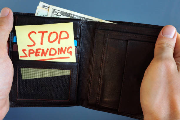Hands holding wallet with stick Stop spending. Hands holding wallet with stick Stop spending. money to burn stock pictures, royalty-free photos & images