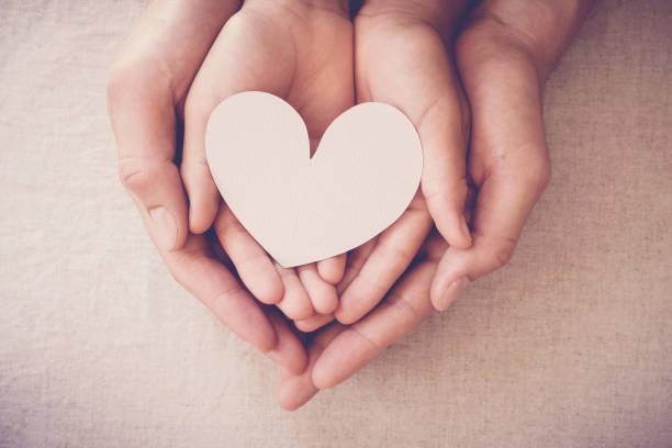 Hände halten weißes Herz, Herzkrankenversicherung, Spendenhilfsorganisation, Pflegekindkonzept – Foto