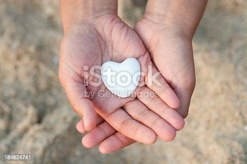 A DSLR photo of two hands holding a white stone heart, taken outside at the beach on defocused sand background. The hands shows the stone heart and offers it as a symbol of life, health care, medicine and share. More hearts...