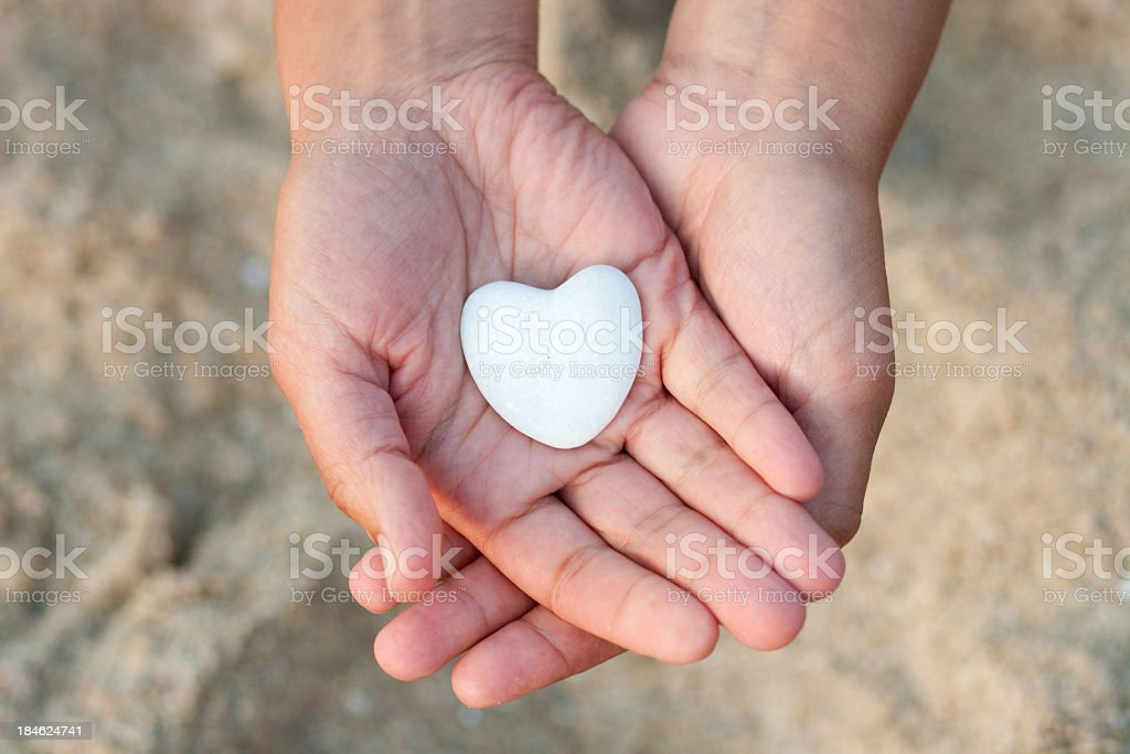 Hands holding white heart-shaped pebble on the beach stock photo
