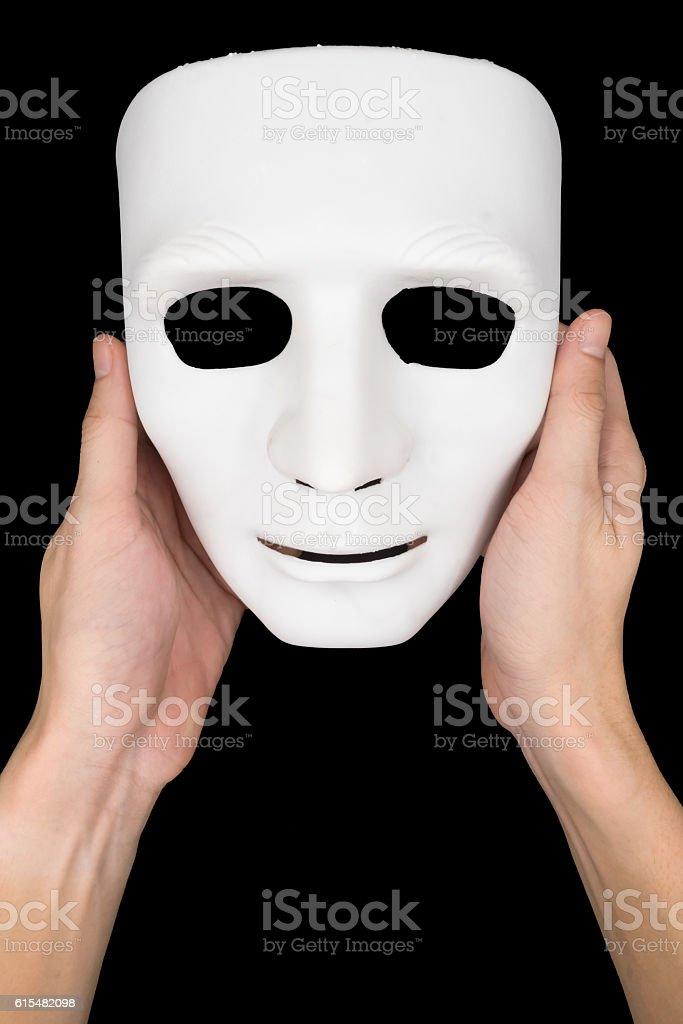 Hands holding white mask on black background. stock photo