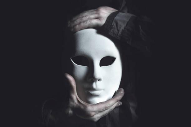 hands holding white mask stock photo