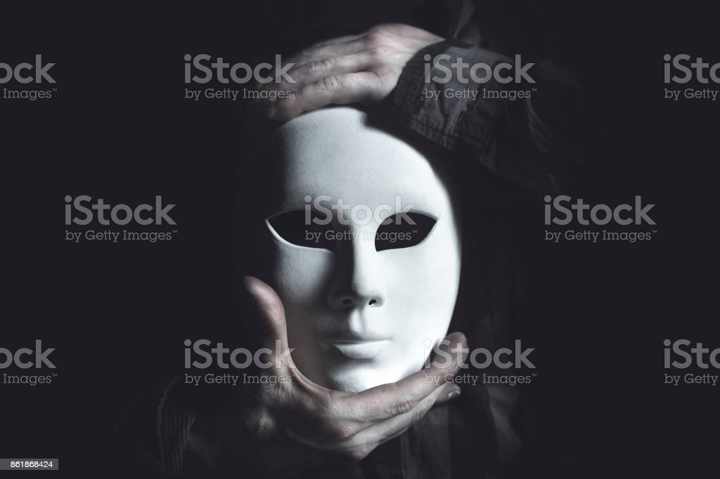 hands holding white mask stock photo