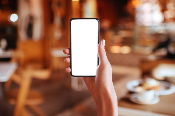 Hands holding white screen smartphone on blurred background. stock photo