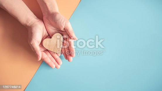 Hands holding wood heart on blue and orange color paper background, health care, love, organ donation.