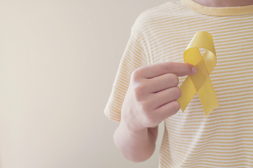 Hands holding yellow gold ribbon, Sarcoma Awareness, Bone cancer, childhood cancer awareness, September yellow, World Suicide Prevention Day concept