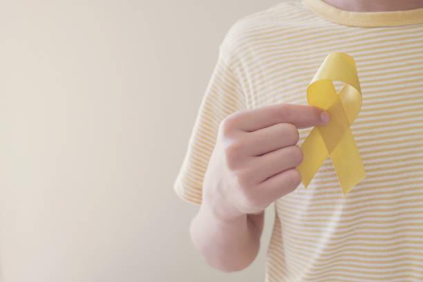 mãos segurando fita de ouro amarelo, conscientização sarcoma, câncer ósseo, conscientização sobre o câncer infantil, setembro amarelo, conceito do dia mundial de prevenção do suicídio - setembro amarelo - fotografias e filmes do acervo