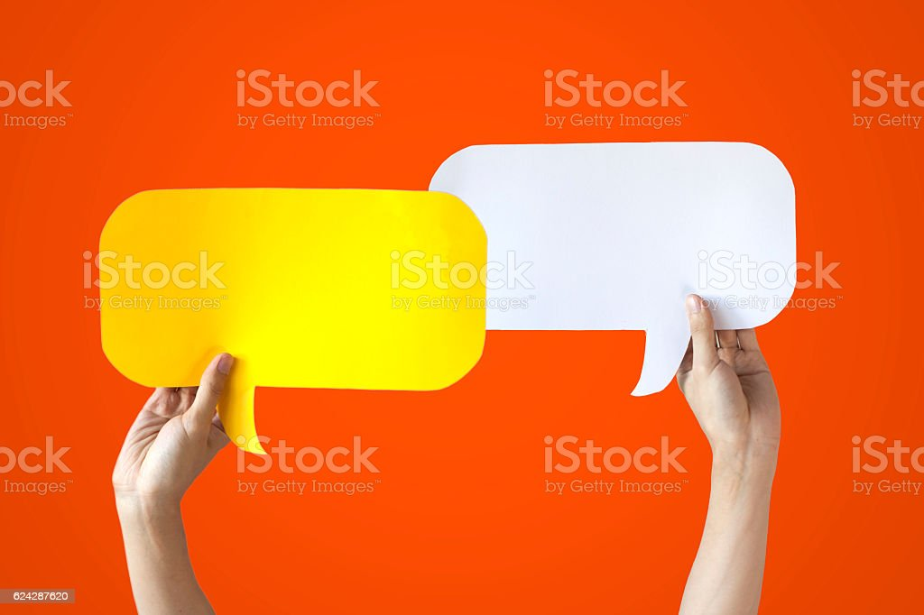Hands Holding Yellow & White Speech Bubbles Over Orange Background - foto de stock